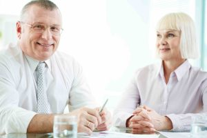 Portrait of smiling boss looking at camera at workplace with mature woman looking at him near by
